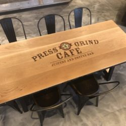 custom logo press & grind white oak plank table with steel banding accompanied with antique gold metal side chairs